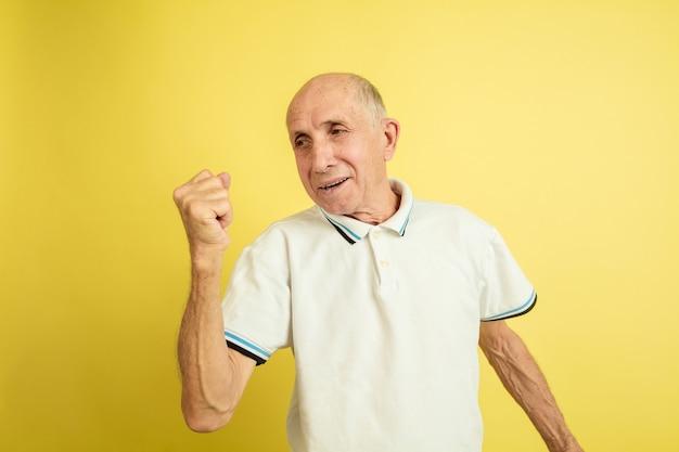 승리를 축하합니다. 노란색 스튜디오 배경에 고립 된 백인 수석 남자의 초상화. 아름다운 남성 감정 모델. 인간의 감정, 표정, 판매, 웰빙, 광고의 개념. copyspace.
