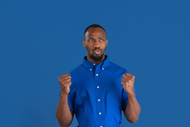 勝利を祝う。青い壁に隔離された若いアフリカ系アメリカ人男性のモノクロの肖像画。美しい男性モデル。人間の感情、顔の表情、販売、広告のコンセプト。若者文化。