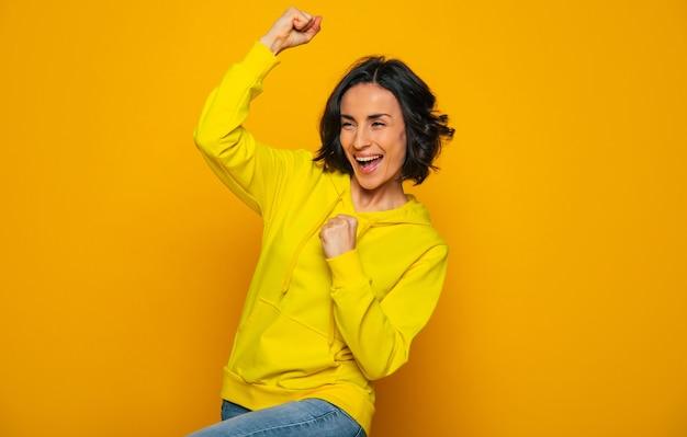 勝利を祝う。黄色いパーカーに身を包んだ笑顔の幸せな女の子、くいしばられた握りこぶしで勝利を祝って、横向きに。