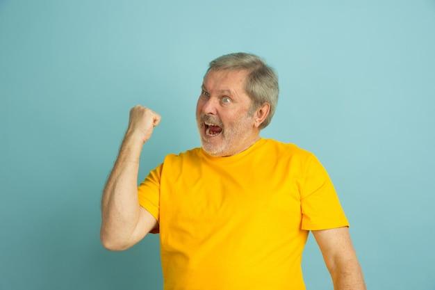 勝利を祝う、スポーツ。青いスタジオの背景に分離された白人男性の肖像画。黄色いシャツのポーズで美しい男性モデル。