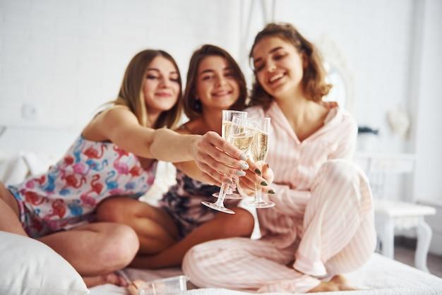 手にアルコールのグラスで祝う。寝室でパジャマパーティーで楽しい時間を過ごしている幸せな女性の友人。