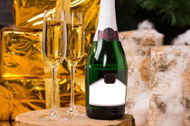 クリスマス、新年、または記念日のために、空白のラベルが付いたボトルと金の紙で包まれたエレガントなギフトで包まれたボックスの横に立っている2つのフルフルートを備えた豪華なシャンパンで祝う
