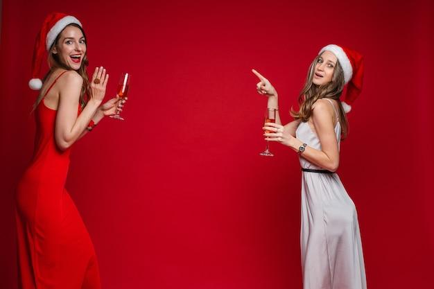 赤い背景にポーズをとってシャンパンでサンタの帽子とお祝いのイブニングドレスで女性の友人を祝う