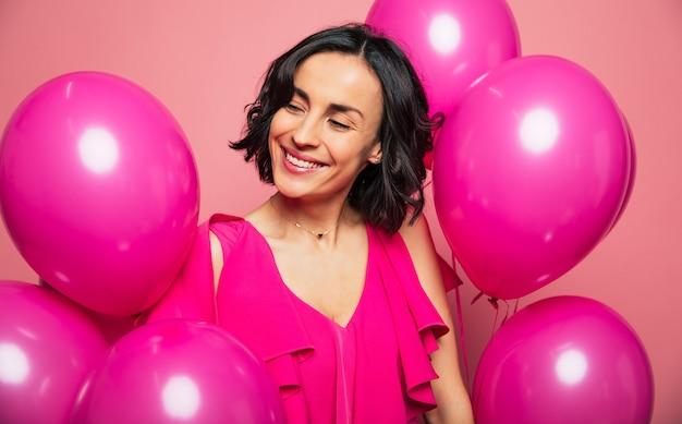 Празднование женского дня. молодая брюнетка в розовом наряде улыбается и смотрит в сторону, окруженная яркими воздушными шарами.