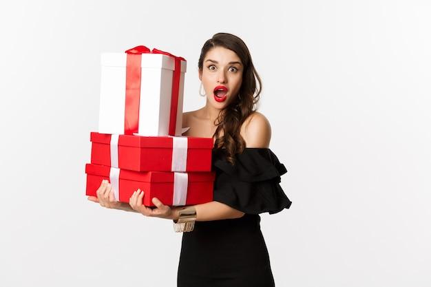 축 하 및 크리스마스 휴일 개념입니다. 검은 드레스 선물을 들고 놀 찾고, 흰색 배경 위에 서있는 아름 다운 여자.