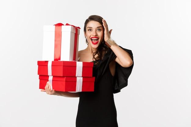 お祝いとクリスマス休暇のコンセプト。興奮して幸せな女性は、白い背景の上に黒いドレスを着て立って、クリスマスプレゼントを持って喜んで贈り物を受け取ります。