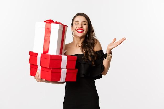 축 하 및 크리스마스 휴일 개념입니다. 흥분하고 행복한 여자는 흰색 배경 위에 검은 드레스에 서서 크리스마스 선물을 들고 기뻐하는 선물을받습니다.