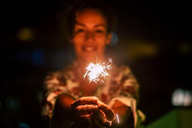 夜に線香花火を持つ陽気な女性とのお祝いと幸福のコンセプト