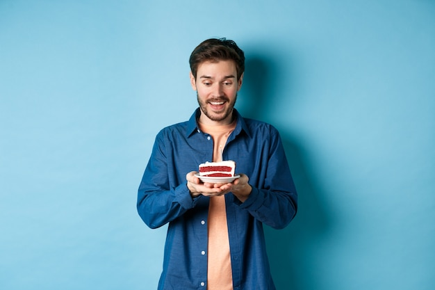 축 하 및 휴가 개념. 생일 케이크를보고 하 고 파란색 배경에 서있는 소원을 만드는 행복 한 젊은 남자.