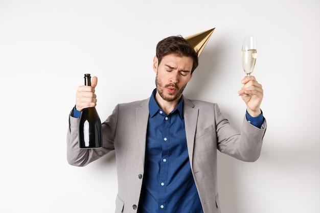 축 하 및 휴일 개념. 술 취한 남자 생일 모자와 정장 파티에서 춤을 추고, 샴페인 잔을 높이고, 이벤트, 흰색 배경에서 재미.