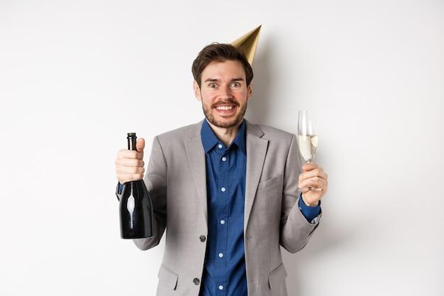 축 하 및 휴일 개념. 웃 고, 샴페인을 마시고 재미, 흰색 배경 파티 모자에 흥분된 잘 생긴 생일 남자.