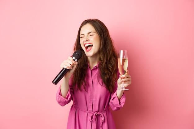 축 하 및 휴일 개념. 파티 아가씨 재미, 샴페인을 마시고 노래방 노래, 마이크를 잡고 분홍색 벽에 행복 서.