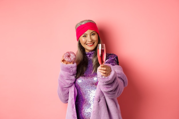 축 하 및 휴일 개념입니다. 세련된 아시아 노인 여성은 파티에서 즐거운 시간을 보내고 달콤한 도넛을 먹고 샴페인 한 잔으로 손을 내밀며 환호, 분홍색 배경을 말합니다.