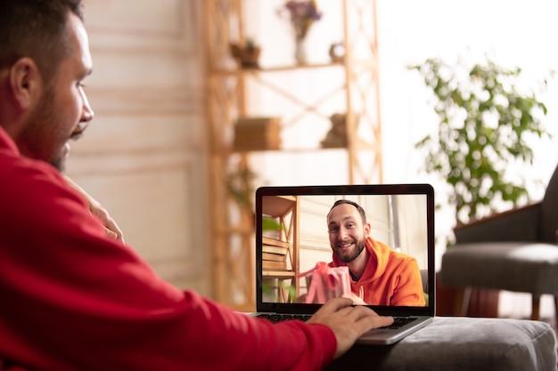 検疫の概念中のお祝いや休日。ビデオハングアウトを使用して話している間、友人または家族は贈り物を開梱します。幸せで、陽気で、誠実に見えます。新年のコンセプト、テクノロジー、感情。