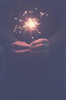 夜の暗闇の中で発射されたスパークラーと手のペアのクローズアップでお祝いと希望の未来のコンセプト-大晦日とコピースペースのあるお祝いの画像