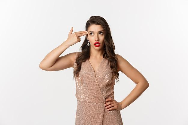お祝いとパーティーのコンセプト。エレガントなイブニングドレスを着たイライラした女性は、退屈から自殺したい、頭の中で指銃を撃ち、イライラした目を転がし、白い背景の上に立っている