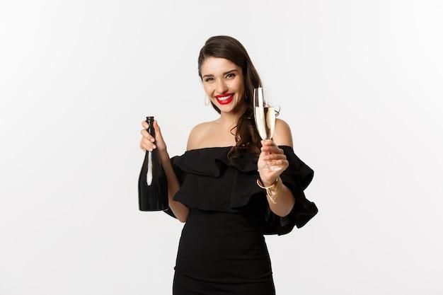 お祝いとパーティーのコンセプト。新年を楽しんで、シャンパングラスを上げて乾杯、白い背景の上の黒いドレスに立って幸せな女性
