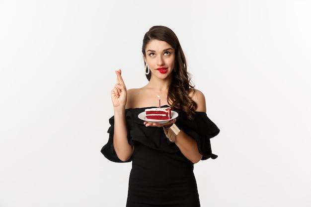お祝いとパーティーのコンセプト。バースデーケーキに願い事をし、指を交差させ、白い背景の上に立って幸せそうに笑って、希望と夢のような女性。