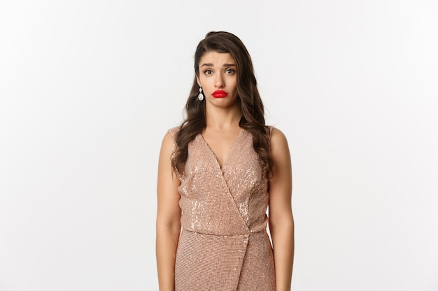 Концепция празднования и вечеринки. грустная и сбитая с толку молодая женщина в гламурном платье, смотрящая на огорченную камеру, стоя на белом фоне.