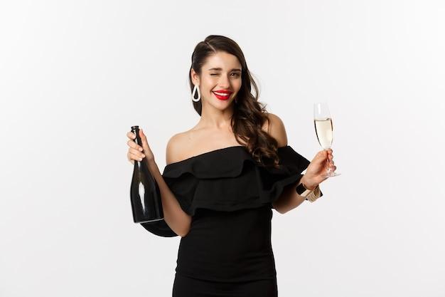 お祝いとパーティーのコンセプト。新年の休暇を楽しんで、シャンパンのボトルとグラスを保持している魅力的なドレスを着たスタイリッシュなブルネットの女性。