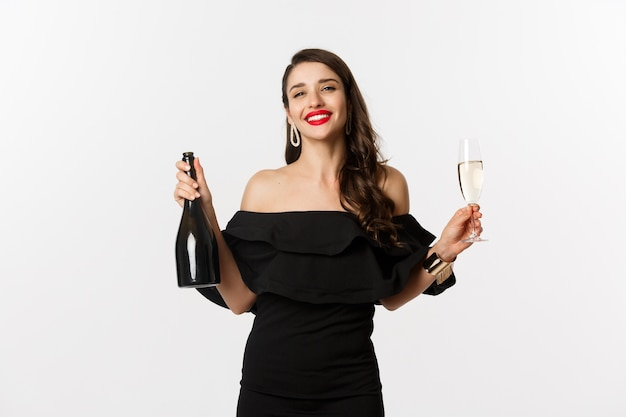 お祝いとパーティーのコンセプト。魅力的なドレスのスタイリッシュなブルネットの女性は、ボトルとシャンパングラスを保持し、満足して笑って、白い背景の上に立っています。