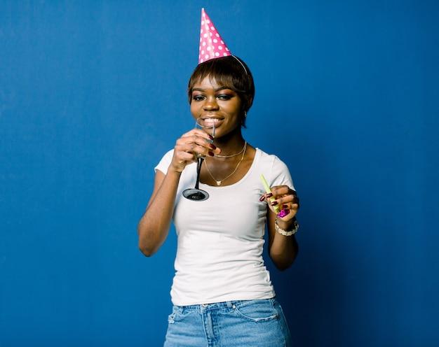 축하와 파티. 재밌어요 흰색 tshirt와 청바지와 생일 모자에 젊은 꽤 아프리카 여자 웃 고있다. 푸른 공간으로 화려한 스튜디오 초상화입니다.