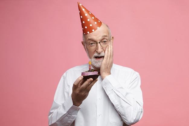 Celebration and anniversary concept. emotional senior man with thick gray beard dressed in fancy elegant clothes, holding birthday cake and touching face in shock, stunned with surprise party