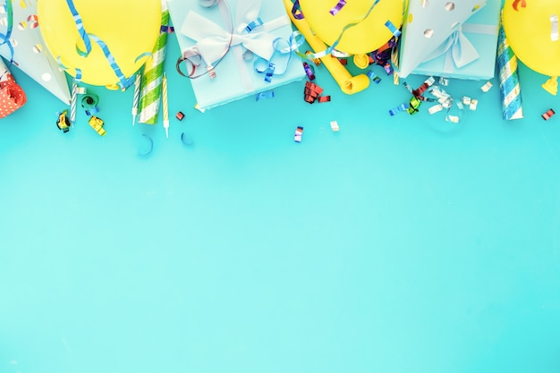 Celebration background with gift box, colorful party streamers, confetti and birthday party hats on blue