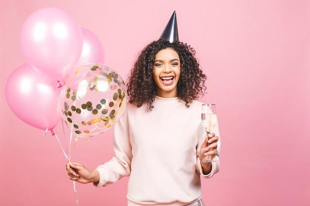 축하 생일 개념-화려한 파티 풍선과 샴페인 핑크 티셔츠와 함께 행복 쾌활한 젊은 아름다운 아프리카 계 미국인 여자의 초상화를 닫습니다