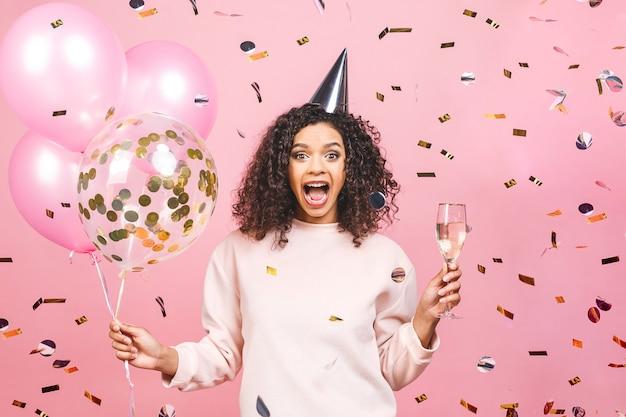 축하 생일 개념-화려한 파티 풍선, 색종이, 샴페인 핑크 티셔츠와 함께 행복 쾌활한 젊은 아름다운 아프리카 계 미국인 여자의 초상화를 닫습니다