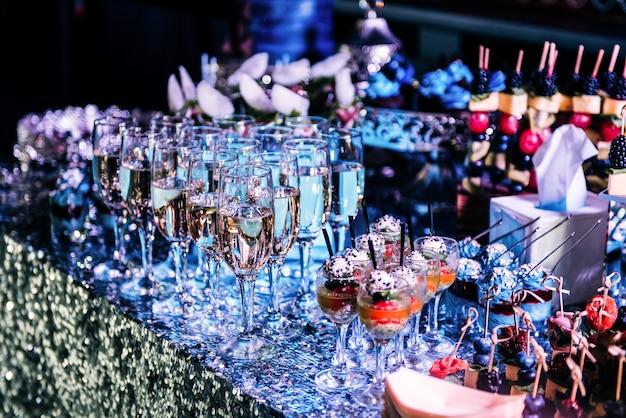 お祝い。スナックとビュッフェテーブルのシャンパングラス。ソフトな色合いのセレクティブフォーカス。