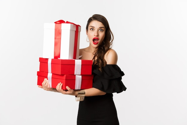 Celebration and christmas holidays concept. beautiful woman in black dress holding gifts and looking surprised, standing over white background.