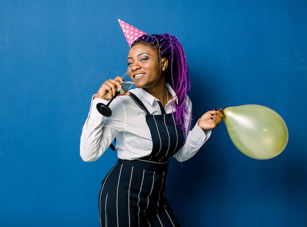 Celebration concept, birthday party - close up portrait happy young beautiful african woman in black pants and white skirt smiling with colorful yellow party balloon. blue pastel studio space.