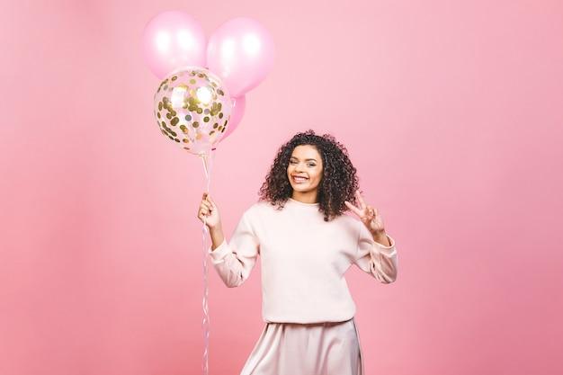 お祝いのコンセプト-カラフルなパーティー風船とピンクのtシャツで幸せな陽気な若い美しいアフリカ系アメリカ人女性の肖像画を閉じます。ピンクのスタジオの背景に対して隔離。