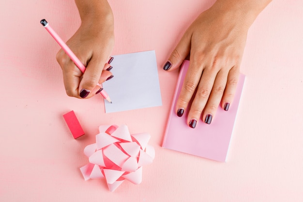 Celebration concept with bow, mini notebook, eraser on pink table flat lay. woman writing on sticky note.