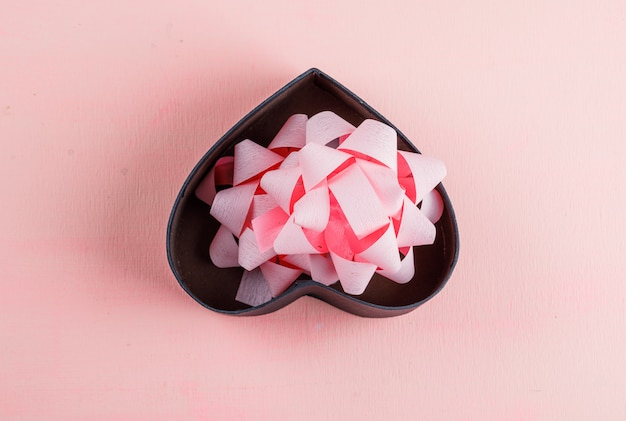 Концепция празднования с лентой лук в подарочной коробке на плоской розовой таблицы лежал.