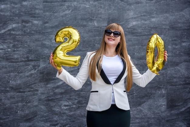 金色の風船を使ったお祝いのコンセプト。灰色の背景に気球を保持しているスーツを着た若い女性