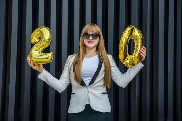 金色の風船でお祝いのコンセプト。灰色の背景に気球を保持しているスーツの若い女性