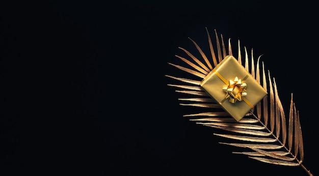 어두운 배경에 잎을 모의와 금 선물 상자 장식으로 축하 개념. 기념일 및 디자인을주는
