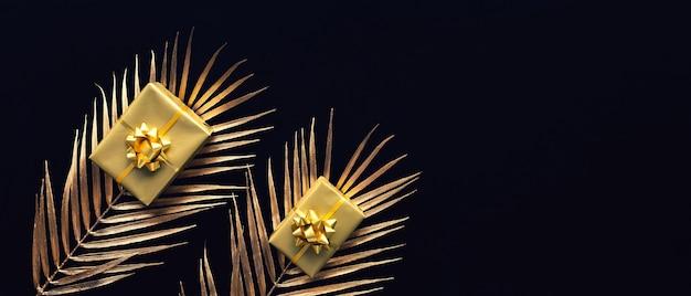 暗い背景にモックアップの葉とゴールドのギフトボックスの装飾とお祝いの概念。記念日とデザインを与える