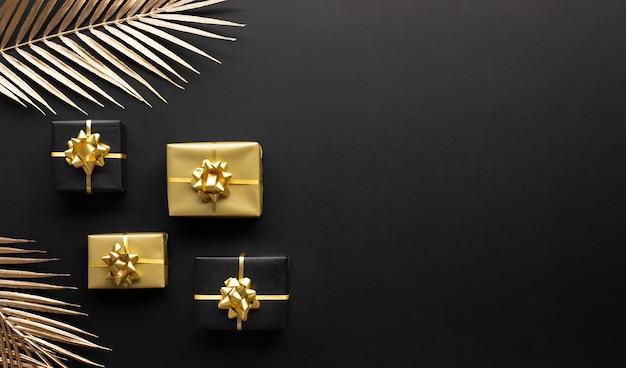 Концепции празднования с украшением золотой подарочной коробки с макетом листа на темном фоне.