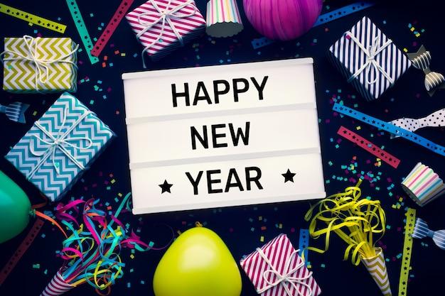 シネマライトボックスとカラフルな要素の新年あけましておめでとうございますのテキストでお祝いの概念