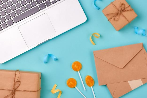 黄色の背景にお祝いの封筒、誕生日パーティーのものとラップトップ