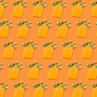 黄色の背景に春の花のチューリップとお祝いの封筒のパターン。グリーティングポストカード。