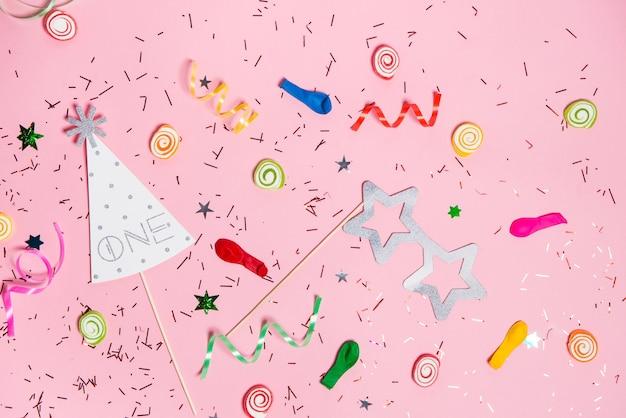 お祝いフラットレイ。ピンクの背景にカラフルなパーティーアイテムとキャンディー。