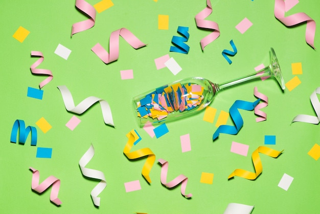 Celebration flat lay with colorful party items on green background.
