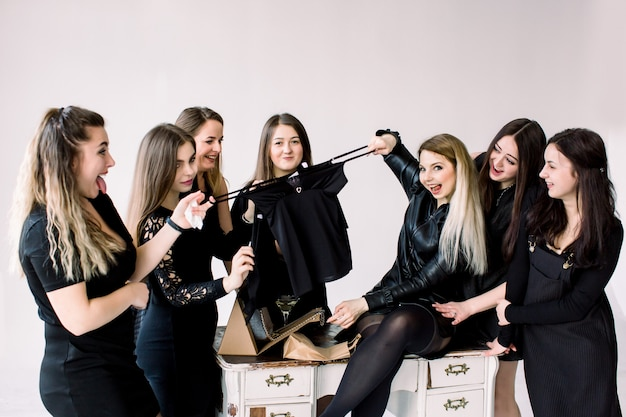 Celebration, friends, bachelorette, birthday party and holidays concept - happy women in black dresses with drink glasses giving presents to birthday girl
