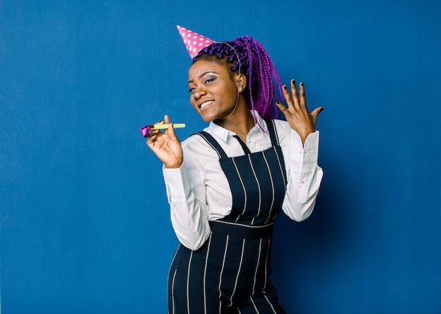 축하, 친구, 처녀 파티, 생일 개념-아프리카 계 미국인 여자 핑크 파티 모자를 쓰고 호의 호른을 불고 미소