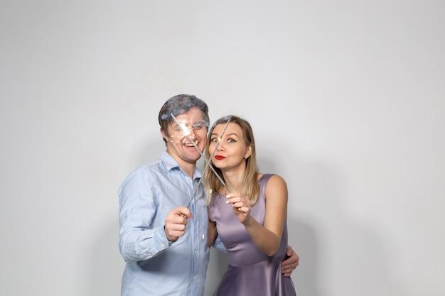 축하, 재미, 휴가 개념 - 행복한 남자와 여자는 폭죽이나 폭죽을 들고 있습니다.