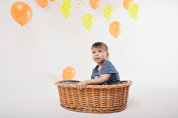 Celebration, fun time spending - children in the basket on a white background among the colored balls celebrate their birthday